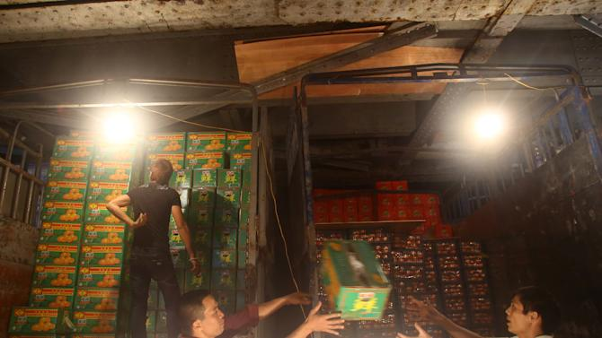 In this March 9, 2013 photo,  porters unload boxes of Chinese oranges at Long Bien wholesale market for fruits and vegetables in Hanoi, Vietnam. Around half of the produce at the market is trucked in from China, arriving in the city in the middle of the night and distribute for Hanoi and neighbor areas. China has emerged as one of the world's leading exporters of fruit and vegetables, and is increasingly taking market share from U.S. producers in Asian markets. It grows more apples than any other country. There are no figures on how much of the crop Vietnam imports. Chinese fruit is often cheaper than Vietnamese, and offers more variety.(AP Photo/Na Son Nguyen)