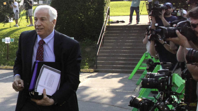 Former Penn State University assistant football coach Jerry Sandusky, left,  arrives at the Centre County Courthouse in Bellefonte, Pa., Wednesday, June 20, 2012. Sandusky is charged with 51 counts of child sexual abuse involving 10 boys over a period of 15 years.  (AP Photo/Gene J. Puskar)