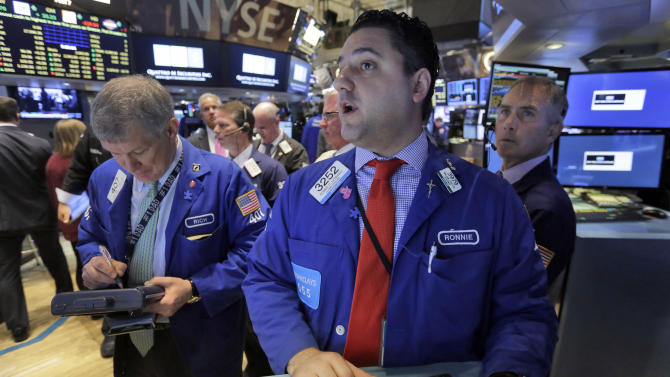 Specialist Ronnie Howard, foreground center, works with traders at his post on the floor of the New York Stock Exchange, Tuesday, June 30, 2015.  U.S. stocks are rising broadly in early trading as investors hope for a last-minute deal on Greece's debt woes. (AP Photo/Richard Drew)