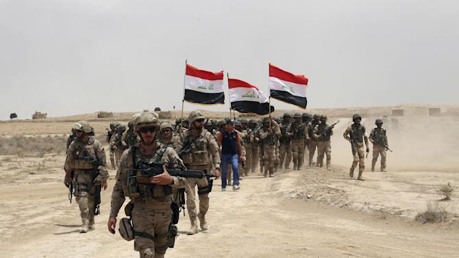 Spanish soldiers advance Iraqi soldiers during a training mission outside Baghdad, Iraq, Wednesday, May 27, 2015. Islamic State extremists unleashed a wave of suicide attacks targeting the Iraqi army in western Anbar province, killing at least 17 troops in a major blow to government efforts to dislodge the militants from the sprawling Sunni heartland, an Iraqi military spokesman said Wednesday. (AP Photo/Khalid Mohammed)