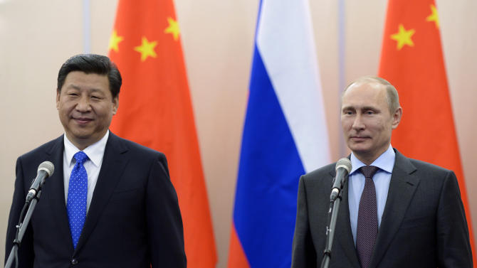 FILE - In this Thursday, Feb. 6, 2014 file photos, Russian President Vladimir Putin, right, and Chinese President Xi Jinping take part in a video conference with commanders of Russian and Chinese navy ships in the Bocharov Ruchei residence in Sochi, Russia. Japanese Prime Minister Shinzo Abe and his Chinese counterpart Xi appear not to be bothered by the international ruckus over Russia's law restricting gay rights. Unlike President Barack Obama, who pointedly declined to attend the Winter Olympics, the leaders of the world's second and third largest economies — where gay rights are not a hot-button political issue — are going to Sochi. (AP Photo/RIA-Novosti, Alexei Nikolsky, Presidential Press Service, File)