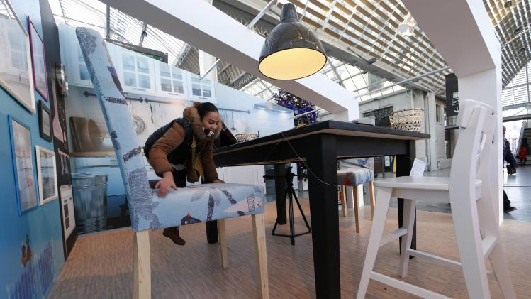 A woman climbs onto an over-sized chair in a display by Swedish furniture giant Ikea at the Gare de Lyon railway station in Paris