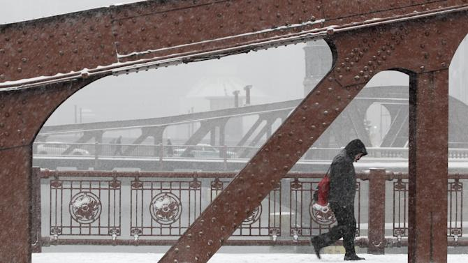 A commuter walks across a Chicago River bridge as a snow storm passes through downtown Chicago Tuesday, March 5, 2013. Chicago was hit Tuesday by a storm expected to dump as much as 10 inches of snow in the area before the end of the day — the most since the 2011 blizzard and its more than 20 inches of snow. (AP Photo/Kiichiro Sato)
