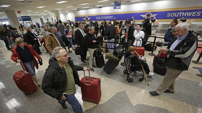 Stranded passengers wait in line at the Southwest ticket counter at the Salt Lake City Airport Thursday, Jan. 24, 2013. The Salt Lake City International Airport was closed due to icy conditions. A Frontier airplane slid on the runway during landing Thursday morning, but nobody was injured. Five flights were canceled and 15 other planes were forced to return to their gates when the runway was closed. The airport is a hub for Delta Airlines. Freezing rain has also caused dozens of accidents on roadways around Salt Lake City this morning.  (AP Photo/Rick Bowmer)