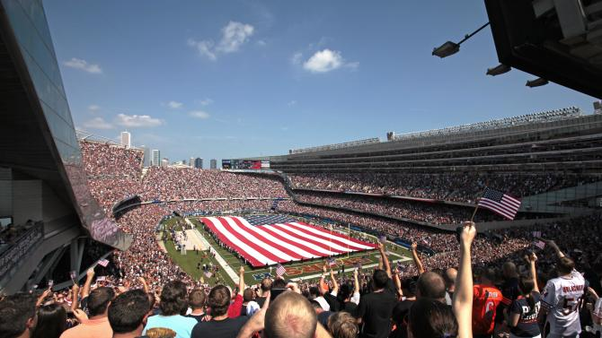 Fan cheer during the national anthem as a giant United States flag is held over Soldier Field on the 10th anniversary of the Sept. 11 attacks before an NFL football game between the Chicago Bears and the Atlanta Falcons in Chicago, Sunday, Sept. 11, 2011. (AP Photo/Kiichiro Sato)