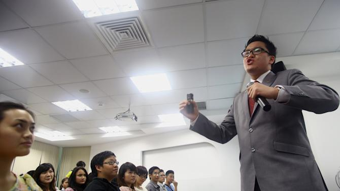 """In this photo taken on Oct. 19, 2012, Australian Brian Tan, right, a """"blue diamond"""" sales executive of Nu Skin, a multilevel marketing company, speaks during a presentation to economic students to expand and recruit distributors for his sales system at Nu Skin's office in Ho Chi Minh City, Vietnam. Nu Skin, which has stormed through Asia over the last two decades, racked up huge profits despite regulatory scrutiny over its marketing practices and the efficacy of the products that it sells. Multilevel marketing businesses have a strained history in China and Vietnam, whose Communist rulers have been wary of pyramid-based sales schemes that have been characterized by some as preying on the dreams of poor citizens. They also fear that unrest as a result of associated scams from the schemes could challenge their legitimacy. (AP Photo/Na Son Nguyen)"""