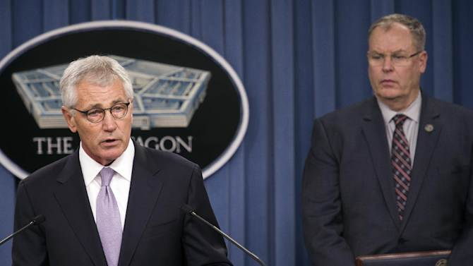 Defense Secretary Chuck Hagel, accompanied by Deputy Defense Secretary Bob Work, briefs reporters at the Pentagon, Wednesday, Oct. 1, 2014, on the military health care system. (AP Photo/Cliff Owen)