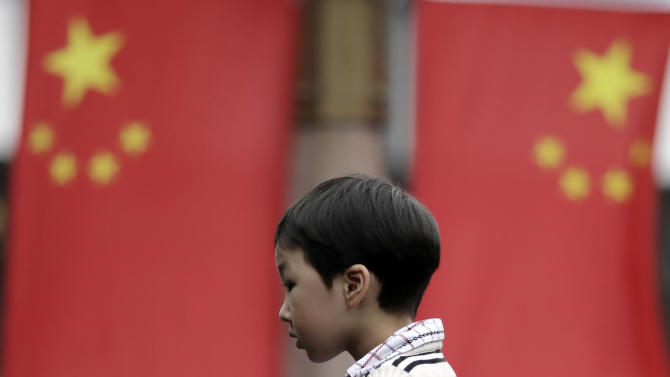 A young visitor walks near Chinese national flags in Shanghai, China, on May Day Tuesday, May 1, 2012. Tens of thousands of Chinese flock to parks and tourist spots to enjoy the May Day holiday. (AP Photo/Eugene Hoshiko)