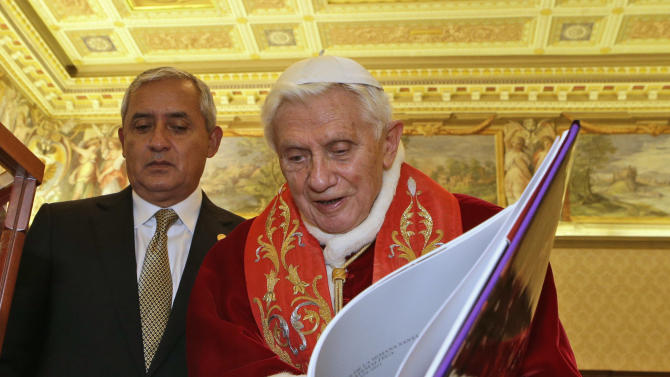 Pope Benedict XVI exchanges gifts with Guatemala's President Otto Perez Molina,  during a private audience at Vatican, Saturday, Feb. 16, 2013. (AP Photo/Alessandra Tarantino,  pool)
