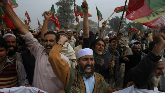 Supporters of Tehreek-e-Insaf or Movement for Justice party chant anti-U.S. slogans during a rally in Peshawar, Pakistan, Saturday, Nov. 23, 2013. Thousands of people protesting U.S. drone strikes blocked a road in northwest Pakistan used to truck NATO troop supplies and equipment in and out of Afghanistan, the latest sign of rising tension caused by the attacks. (AP Photo/Mohammad Sajjad)