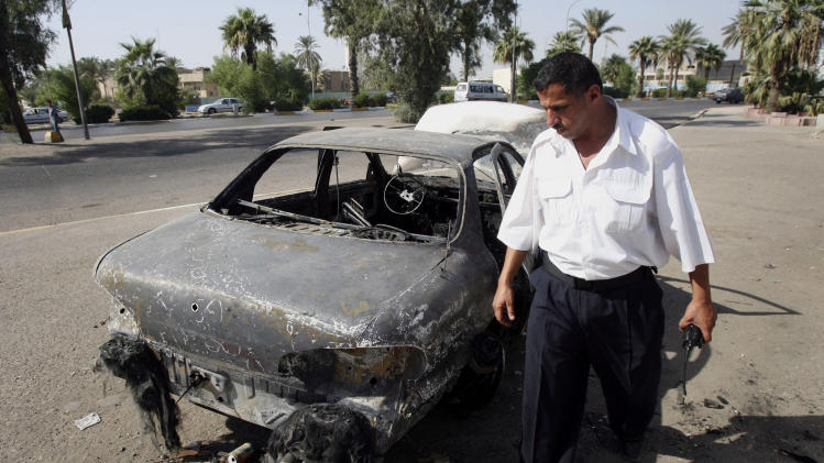 FILE - This Sept. 25, 2007 file photo shows an Iraqi traffic policeman inspecting a car destroyed by a Blackwater security detail in al-Nisoor Square in Baghdad, Iraq. A former Blackwater security guard says he decided to tell the truth about his role in the shooting of 32 Iraqi civilians in a Baghdad square because he wants to move on with his life, even though it might mean he probably will go to prison. Jeremy Ridgeway is testifying against four of his former colleagues who would face long prison terms if convicted of killing 14 Iraqis and wounding 18 others in Nisoor Square. Ridgeway is the prosecution's chief cooperating witness in the case focusing on events that happened seven years ago. He has pleaded guilty to voluntary manslaughter and attempted manslaughter. The trial has been underway for more than one month. (AP Photo/Khalid Mohammed, File)
