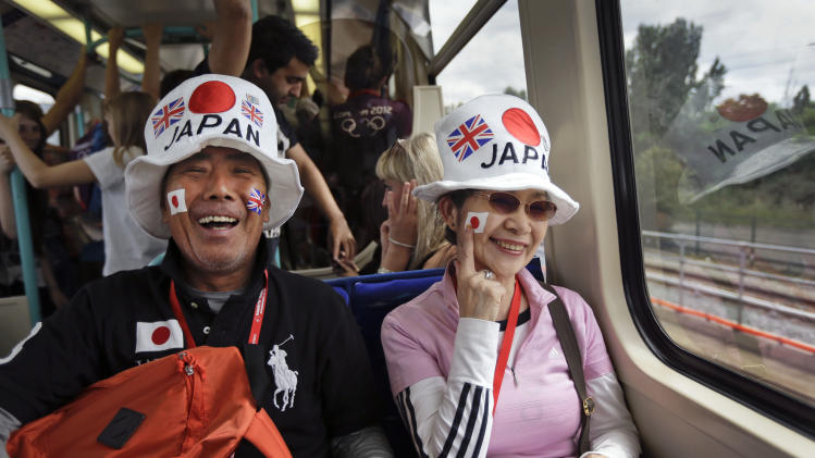 Two visitors from Japan ride the train to go and watch the judo competition at the 2012 Summer Olympics, Saturday, July 28, 2012, in London. (AP Photo/Ben Curtis)