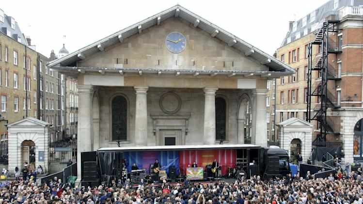 Crowds gather to watch Sir Paul McCartney, on stage centre, and his band in Covent Garden, London, Friday, Oct. 18, 2013. The surprise gig lasted for 20 minutes during lunchtime following a similar appearance in New York last Friday. (Photo by Jonathan Short/Invision/AP)