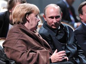 """Russian President Putin and German Chancellor Merkel talk as they watch a fragment from the ballet """"Ruslan and Lyudmila"""" during the G20 Summit in Peterhof near St. Petersburg"""