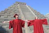 Students celebrate their graduation in front of a replica Mayan pyramid before a countdown by Taiwan's National Museum of Natural Science to help reassure the public it is not the end of the world, in Taichung on December 21, 2012. A global day of lighthearted doom-themed celebration culminated Friday in the jungle temples of the Mayan people of Central America, whose calendar sparks apocalypse fears