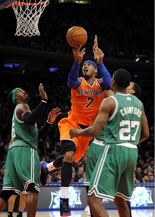 New York Knick' Carmelo Anthony (7) leaps between Boston Celtics' Gerald Wallace (45) and Jordan Crawford (27) to shoot for the basket during an NBA basketball game on Sunday, Dec. 8, 2013, in