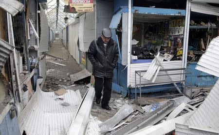 A man walks past a shop which was recently damaged by shelling, at a local market in Donetsk