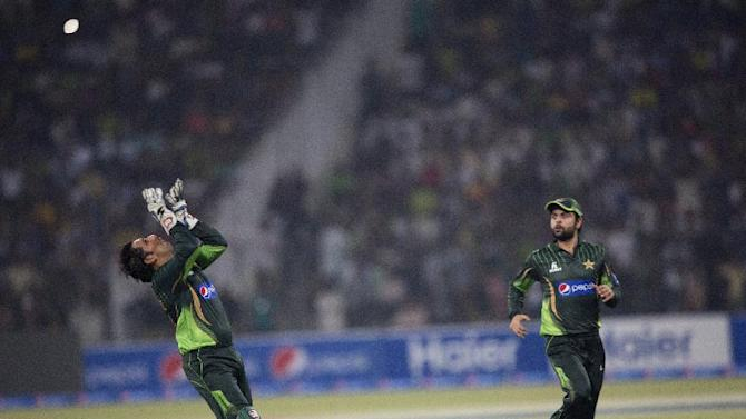 Pakistan's wicketkeeper Sarfraz Ahmed about to catch Zimbabwe's Vusimuzi Sibanda as Pakistan's Ahmed Shahzad looks on at the Gaddafi stadium in Lahore, Pakistan, Friday, May 22, 2015. Zimbabwe is the first test-playing team to visit this country since gunmen attacked the Sri Lanka team outside this venue in 2009, canceling all major tours to Pakistan until now. (AP Photo/B.K. Bangash)