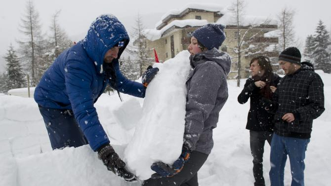 """Members of the Occupy WEF movement build an igloo at their camp site two days before the opening of the 42nd Annual Meeting of the World Economic Forum, WEF, in Davos, Switzerland, Monday, Jan. 23, 2012. The overarching theme of the Meeting, which will take place from 25 to 29 January, is """"The Great Transfomation: Shaping New World"""". (AP Photo/Keystone/Jean-Christophe Bott)"""