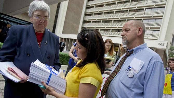 """Sister Mary Ann Walsh, left, director of media relations for the U.S. Conference of Catholic Bishops, accepts a petition from Erin Saiz Hanna with the Nun Justice Project at the U.S. Bishops' biannual meeting Wednesday, June 13, 2012, in Atlanta. Supporters of U.S. Catholic nuns hand delivered the petition in response to a recent Vatican finding, which accused them of promoting """"certain radical feminist themes incompatible with the Catholic faith,"""" while failing to emphasize core teaching on abortion. The Vatican ordered a full-scale overhaul of the organization overseen by three American bishops, a decision that has led to an outpouring of support for the nuns nationwide. (AP Photo/David Goldman)"""