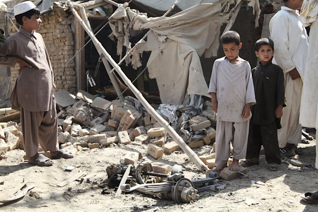 Afghan children stand near the wreckage of a vehicle after an explosion in Kandahar, south of Kabul, Afghanistan, Monday, July 9, 2012. Three suicide bombers riding a three-wheeled vehicle blew themselves up Monday afternoon in Kandahar city, killing two children and wounding several other civilians, said Kandahar provincial spokesman Ahmad Jawed Faisal. He said authorities had not determined the target of the explosion. (AP Photo/Allauddin Khan)
