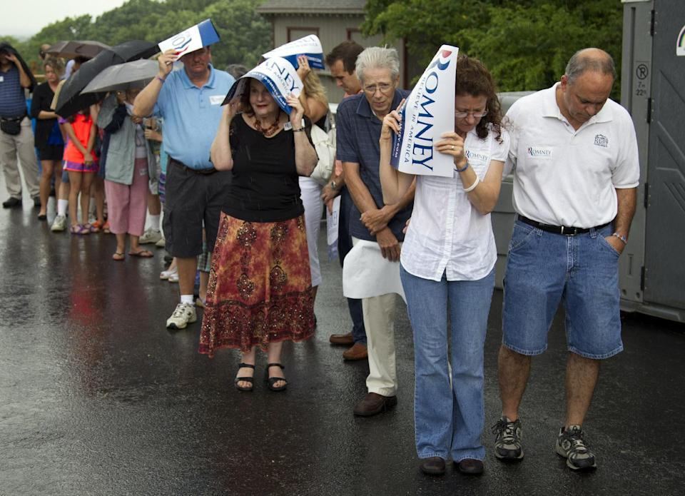 Supporters of Republican presidential candidate, former Massachusetts Gov. Mitt Romney wait in the rain for his arrival to a campaign stop at Mapleside Farms on Sunday, June 17, 2012 in Brunswick, Ohio.  (AP Photo/Evan Vucci)
