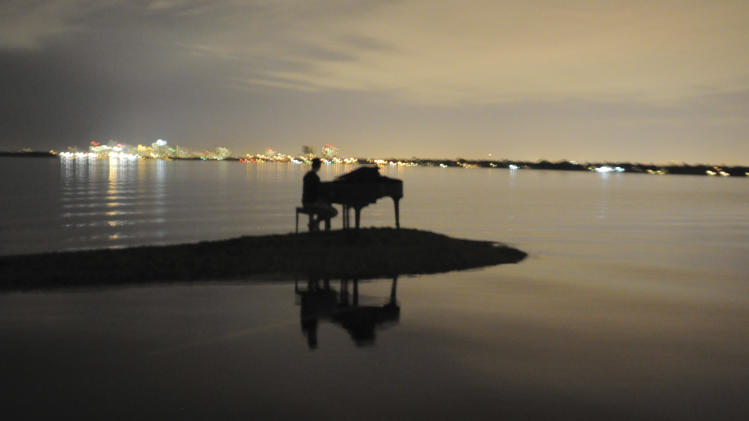 In this Jan. 2, 2011 photo provided by Nicholas Harrington, Julian Kolevris-Roots, 18, is shown sitting at a piano on a sandbar in Miami's Biscayne Bay.  Harrington, a 16-year-old looking to boost his college application, says he is responsible for putting a grand piano on a Biscayne Bay sandbar. (AP Photo/Nicholas Harrington)