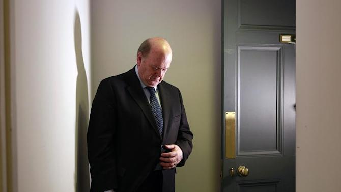 Irish Minister for Finance Michael Noonan adjusts his suit blazer after an interview with Reuters at his offices in central Dublin