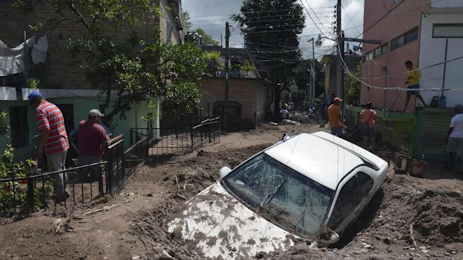 A car lays buried in mud after flooding triggered by Tropical Storm Manuel as residents try to clean up their neighborhood in Chilpancingo, Mexico, Thursday, Sept. 19, 2013. Manuel, the same storm that devastated Acapulco, gained hurricane force and rolled into the northern state of Sinaloa on Thursday before starting to weaken. (AP Photo/Alejandrino Gonzalez)