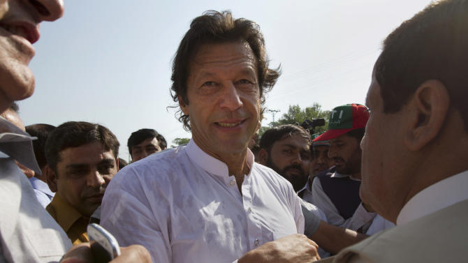 "FILE - In this Saturday, Oct. 6, 2012 file photo, Pakistan's ex-cricket star-turned-politician Imran Khan, center, is surrounded by his supporters as he arrives to lead what organizers are calling the ""peace march,"" in Islamabad, Pakistan. Khan who founded Pakistan Tehreek-e-Insaf, or the Movement for Justice Party has appealed to a largely young, urban constituency tired with the current crop of politicians and the corruption that plagues the system. Though analysts doubt his party can win enough seats to form the next government his party could affect who comes out on top in the elections. (AP Photo, File)"