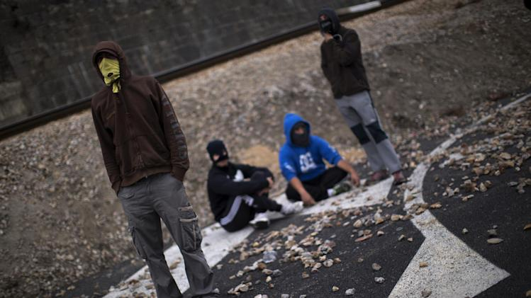 Masked miners sit on the road as they block the traffic in Cinera, near Leon, Spain, Monday, June 11, 2012. Strikes, road blockades, and mine sit-ins continue as 8,000 mineworkers at over 40 coal mines in northern Spain continue their protests against government action to cut coal subsidies. (AP Photo/Emilio Morenatti)