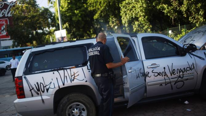 A federal police officer looks inside the vandalized vehicle of Acapulco's Mayor Walton Aburto after a demonstration demanding justice for the 43 missing students from Ayotzinapa Teacher Training College, in Acapulco