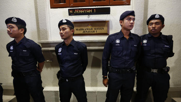 Police stand guard outside a court room in Kuala Lumpur, Malaysia, Thursday, May 23, 2013. Prosecutors filed a sedition charge Thursday against a student activist who urged Malaysians to engage in street protests against the government over claims of election fraud. (AP Photo/Vincent Thian)