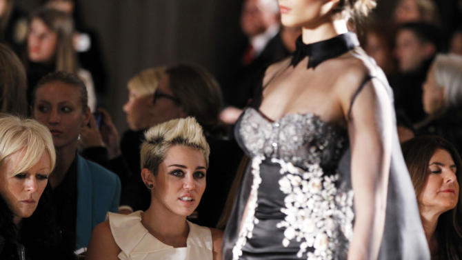 Singer Miley Cyrus watches a model presents a creation from the Marchesa Autumn/Winter 2013 collection during New York Fashion Week