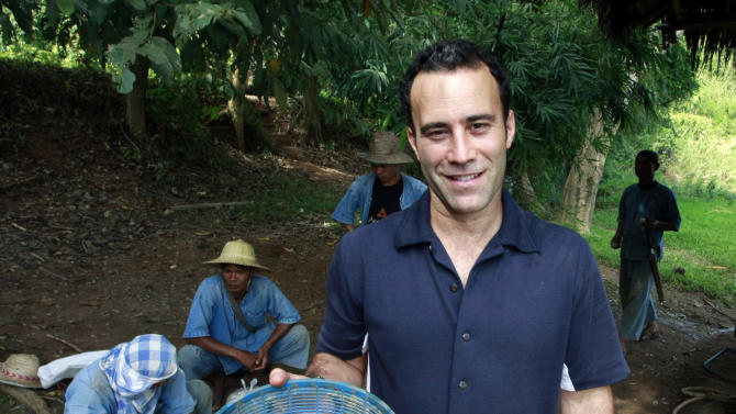 HOLD FOR THAILAND ELEPHANT COFFEE BY JOCELYN GECKE- In this photo taken Dec. 3, 2012, Blake Dinkin, founder of Black Ivory Coffee, holds a basket of coffee beans to mix with other fruits before feeding to elephants at an elephant camp in Chiang Rai province, northern Thailand. Dinkin, 37, a Canadian entrepreneur with a background in civet coffee, has teamed up with a herd of 20 elephants, gourmet roasters and one of the country's top hotels to produce the Black Ivory, a new blend from the hills of northern Thailand and the excrement of elephants which ranks among the world's most expensive cups of coffee. (AP Photo/Apichart Weerawong)