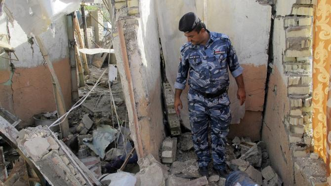 Iraqi policeman inspects the site of a car bomb attack in Baghdad's Kadhimiya district