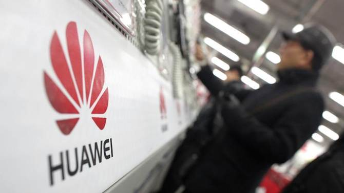 A man looks at a Huawei mobile phone as he shops at an electronic market in Shanghai