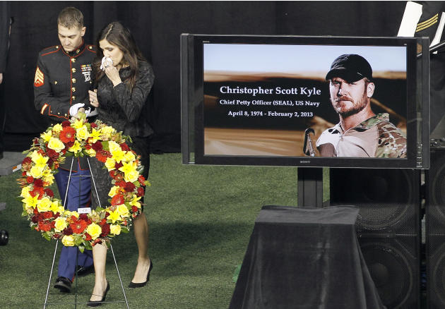 Christopher Kyle's wife, Taya, is escorted to her seat after memorializing her husband during a memorial service at Cowboys Stadium, Monday, Feb. 11, 2013, in Arlington, Texas. Thousands attended the