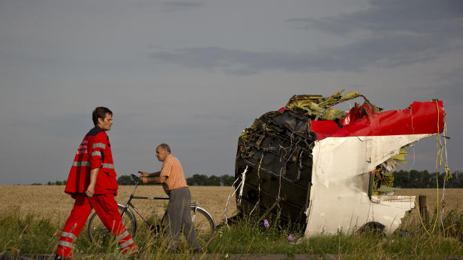 A paramedic walks by a part of fuselage at the crash site of Malaysia Airlines Flight 17 near the village of Hrabove, eastern Ukraine, Saturday, July 19, 2014. World leaders demanded Friday that pro-Russia rebels who control the eastern Ukraine crash site of Malaysia Airlines Flight 17 give immediate, unfettered access to independent investigators to determine who shot down the plane. (AP Photo/Vadim Ghirda)