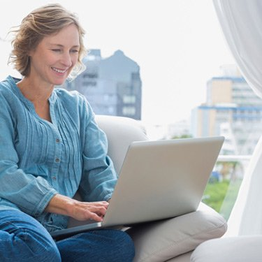 Smiling-blonde-woman-sitting-on-her-couch-using-laptop_web