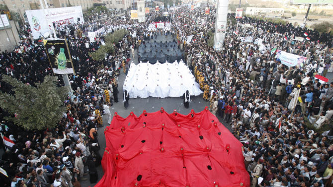 Yemeni pro-democracy protestors march with a big banner in the colors of their national flag during a parade marking the second anniversary of the revolution in Sanaa, Yemen, Monday, Feb. 11, 2013. The 2011 Yemeni Revolution was as an extension of the broader Arab Spring which has toppled four authoritarian leaders to date. Yemenis were able to create a unique revolution, their struggle came peacefully, unarmed, and lead by women and youth. (AP Photo/Hani Mohammed)