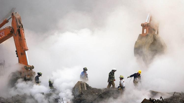 FILE - In this Oct. 11, 2001 file photo, firefighters make their way over the ruins of the World Trade Center through clouds of smoke at ground zero in New York. A decade's worth of study has answered only a handful of questions about the hundreds of health conditions believed to be related to the tons of gray dust that fell on the city when the trade center collapsed, from post-traumatic stress disorder, asthma and respiratory illness to vitamin deficiencies, strange rashes and cancer. .(AP Photo/Stan Honda, Pool)