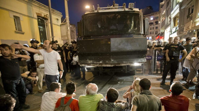 People sit in front of a water cannon truck in Istiklal Avenue in Istanbul, Turkey, Tuesday, July 9, 2013. Gezi Park remained open for the night after thousands of anti-government protesters broke their fast for the holy month of Ramadan by sitting down for a meal along a main Istanbul pedestrian street for a makeshift Ramadan banquet that stretched some 500 meters (yards) toward the city's landmark Taksim Square. (AP Photo/Vadim Ghirda)