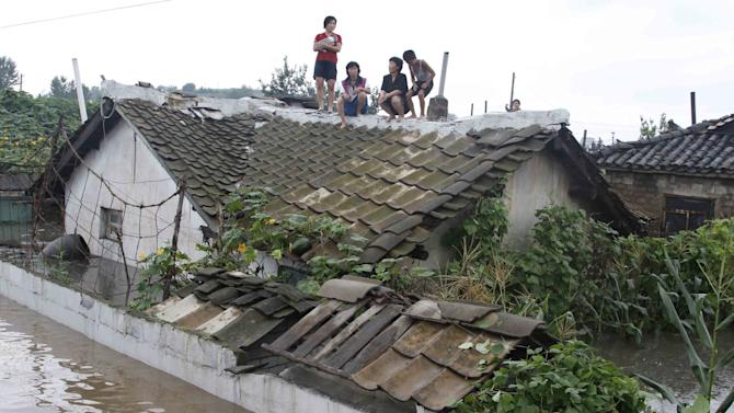 Residents wait on the roof of a flooded building in Anju City, South Phyongan Province, North Korea Monday, July 30, 2012. Officials said 1,000 houses and buildings were destroyed and 2,300 hectares of farmland were completely submerged in the city. (AP Photo/Kim Kwang Hyon)