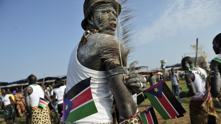 A man holds South Sudanese flags as he prepares to dance at the country's anniversary celebrations, at the John Garang mausoleum in Juba, South Sudan, Monday, July 9, 2012. The world's newest nation, South Sudan, is celebrating its first birthday and while the largest achievement over the last year was avoiding a return to all-out war with Sudan, the south has seen its economy crippled after it shut down its oil industry and thousands of refugees are streaming into the country every week to avoid violence on Sudan's side of the border. (AP Photo/Shannon Jensen)