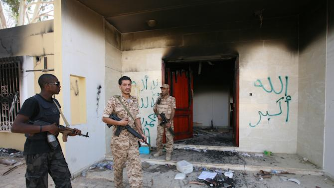 "FILE - In this Friday, Sept. 14, 2012 file photo, Libyan military guards check one of the U.S. Consulate's burnt out buildings during a visit by Libyan President Mohammed el-Megarif, not shown, to the U.S. Consulate to express sympathy for the death of the American ambassador, Chris Stevens and his colleagues in the deadly attack on the Consulate last Tuesday, September 11, in Benghazi, Libya. Britain's Foreign Office urged U.K. nationals to immediately leave the eastern Libyan city of Benghazi in response to an imminent threat against Westerners. The Arabic on the building reads, ""God is Great,  and there is no God but Allah and Mohammed is his messenger."" (AP Photo/Mohammad Hannon, File)"