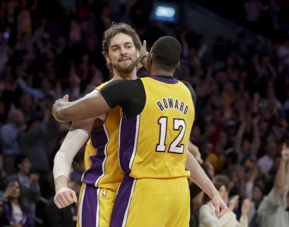 Los Angeles Lakers' Pau Gasol, left, of Spain, and Dwight Howard celebrate their team's 99-95 overtime win against the Houston Rockets after an NBA basketball game in Los Angeles, Wednesday, April 17, 2013. (AP Photo/Jae C. Hong)