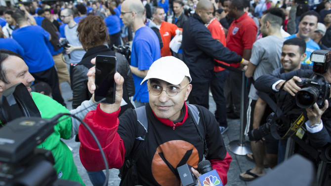 Hazem Sayed, 54, the first in line to purchase the new iPhone 5, holds up his new phone in front of media outside the Fifth Avenue Apple store, Friday, Sept. 21, 2012, in New York. Hundreds of people waited in line through the early morning to be among the first to get their hands on the highly anticipated phone. (AP Photo/John Minchillo)