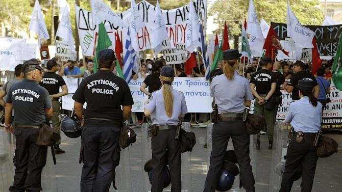 Police officers stand in front of the protesters  during an anti-bailout protest outside of the Cyprus' parliament in capital Nicosia, Tuesday, April 30, 2013. Cyprus' lawmakers are voting Tuesday on a multi-billion bailout agreement aimed at preventing the country from going bankrupt. The 56-seat parliament is expected to narrowly approve the 23 billion-euro ($30 billion) deal that the country struck with its euro partners and the International Monetary Fund last month. (AP Photo/Petros Karadjias)