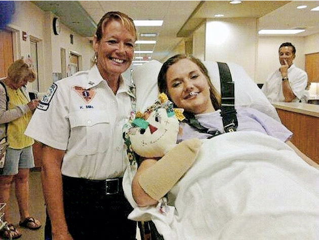 In this image released Monday, July 2, 2012, by Tom Adkins, shows Aimee Copeland, right, with medic Kori Mills as Copeland leaves a hospital in Augusta Ga., headed for an inpatient rehabilitation clin